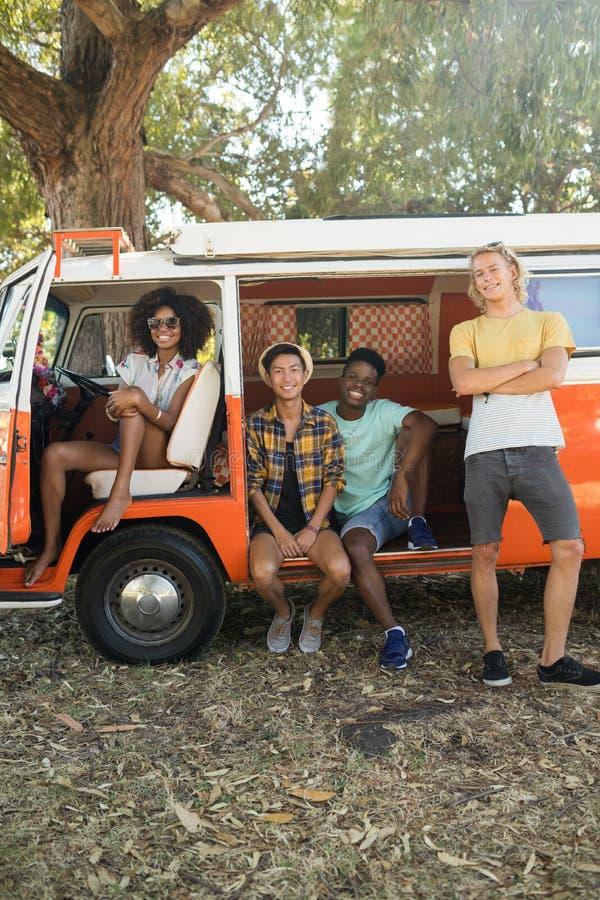 年轻朋友画象有露营者货车的在露营地停放了 免版税库存图片