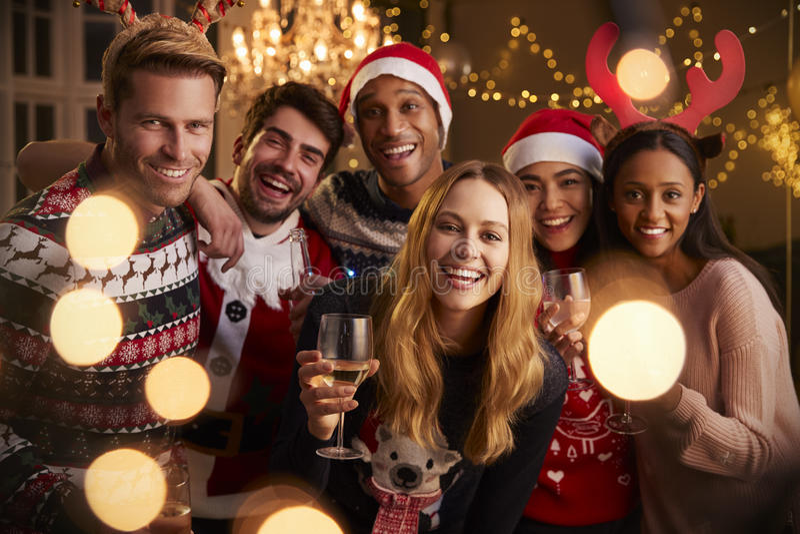 朋友画象欢乐套头衫的在圣诞晚会 免版税库存图片