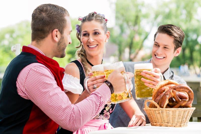 Download 朋友beergarden使叮当响的玻璃用啤酒 库存图片. 图片 包括有 少女装, 巴伐利亚人, 叫化子, 烤肉 - 59102297