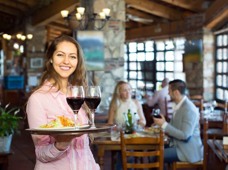 服务一张桌的女服务员在小酒馆 免版税库存照片