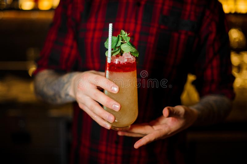服务与小管的侍酒者一个特立尼达Swizzle鸡尾酒在装饰玻璃 免版税库存图片