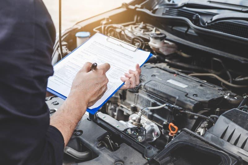 服务发动机机器概念,检查发动机的汽车修理工安装工与检查文字对剪贴板 免版税图库摄影