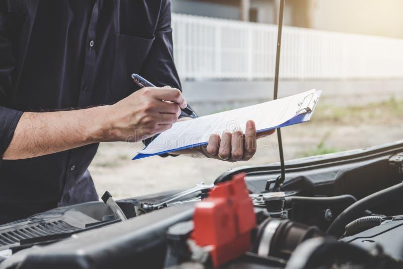 服务发动机机器概念,检查发动机的汽车修理工安装工与检查文字对剪贴板 图库摄影