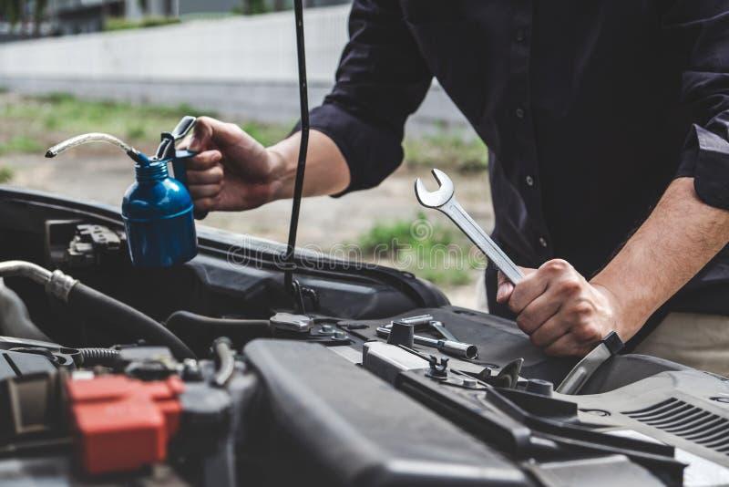 服务发动机机器概念,汽车修理工修理有板钳的安装工手一个发动机汽车车间 免版税图库摄影