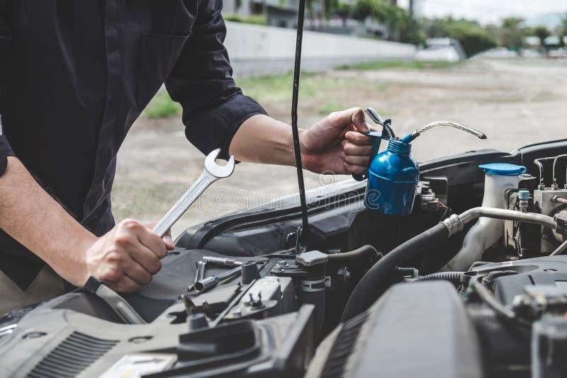 服务发动机机器概念,汽车修理工修理有板钳的安装工手一个发动机汽车车间 免版税库存图片