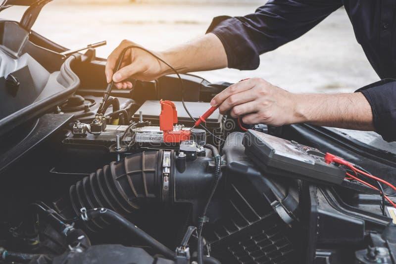 服务发动机机器概念,汽车修理工检查发动机汽车车间的安装工手与数字 库存照片