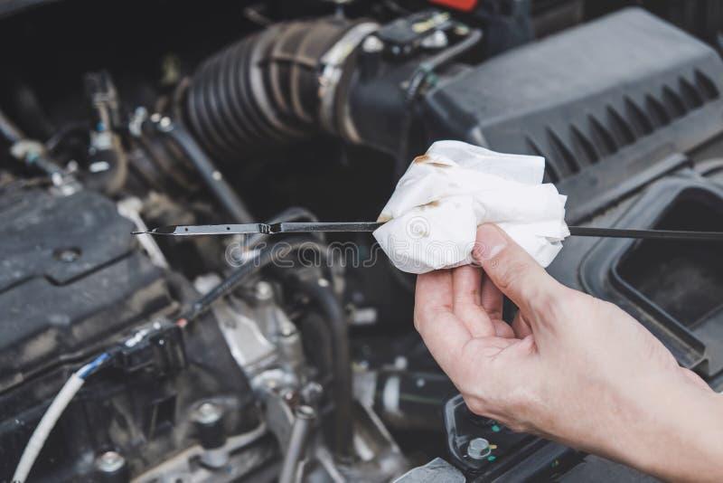 服务发动机机器概念,汽车修理工检查发动机的安装工手汽车与在的油面 免版税库存照片