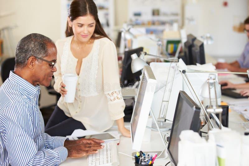 服务台的工作者在繁忙的创造性的办公室 库存照片