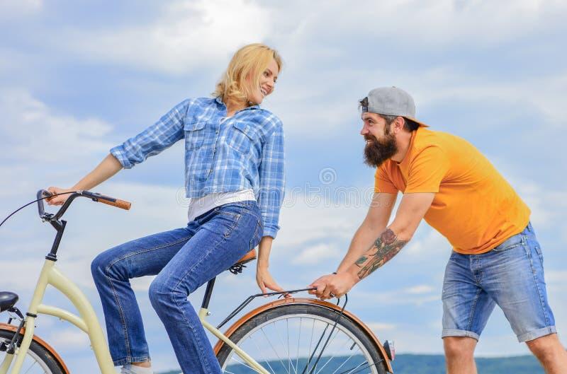 服务和协助 人帮助保留平衡乘驾自行车 循环的女孩,当人支持她时 支持帮助相信  库存图片