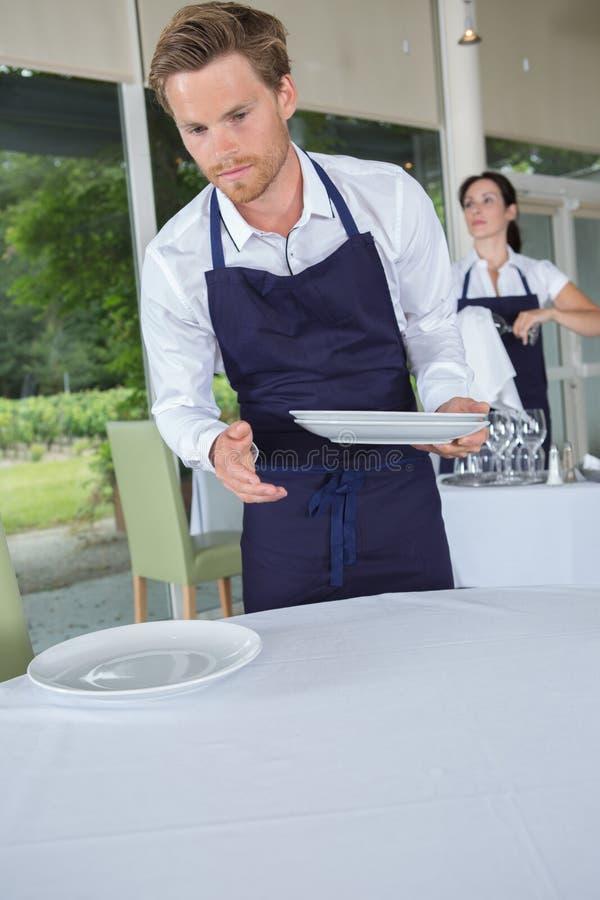 服务器在拿着板材的餐馆 免版税库存照片