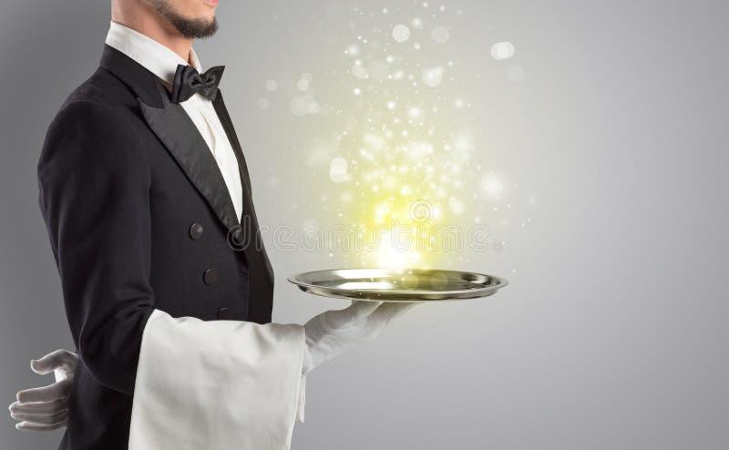 服务在盘子的侍者神奇光 库存图片