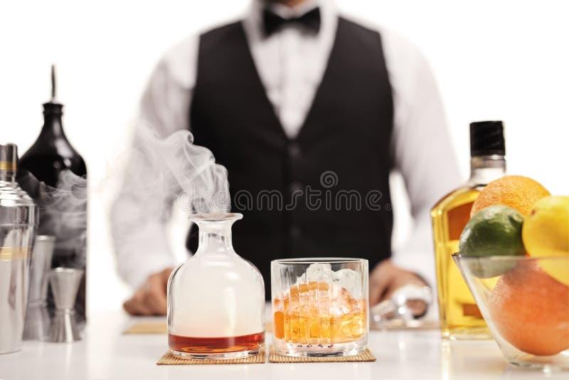 服务威士忌酒鸡尾酒的侍酒者 免版税库存照片