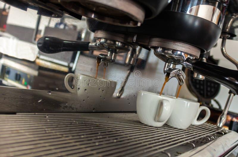服务有反射、蒸汽和水下落的咖啡机两个白色杯子 库存照片