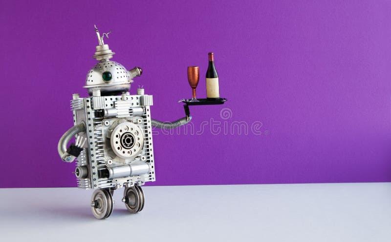 服务有瓶和酒杯的滑稽的机器人侍者一个盘子 两个在紫罗兰色墙壁上的轮子国内机器人字符 库存图片