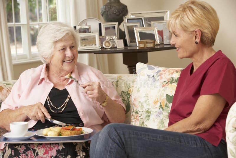 服务有膳食的帮手资深妇女在关心家 库存照片