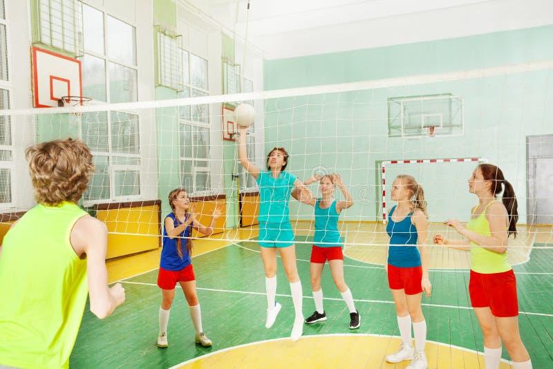 服务球的青少年的女孩在排球比赛期间 免版税库存照片