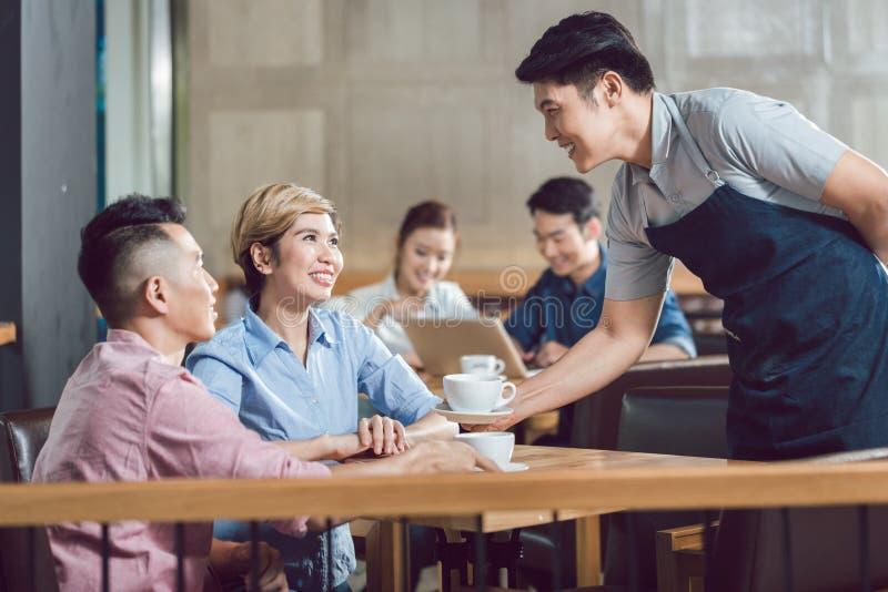 服务用在咖啡馆的咖啡的夫妇 库存照片