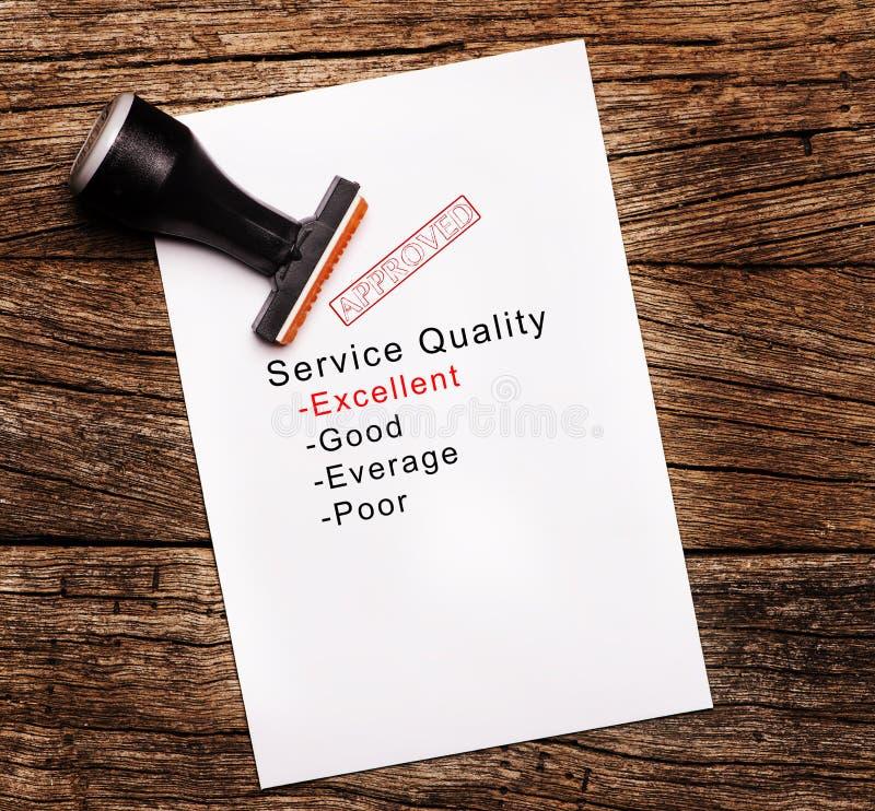 服务质量的优秀评估在纸的在木背景 免版税库存照片