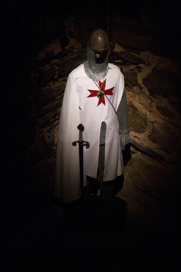 服装一templar与在黑暗的剑有石背景 免版税库存图片