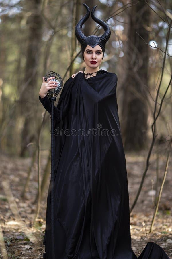 服装戏曲 有摆在有弯曲处的春天空的森林里的垫铁的奇妙和不可思议的有害妇女 免版税库存图片