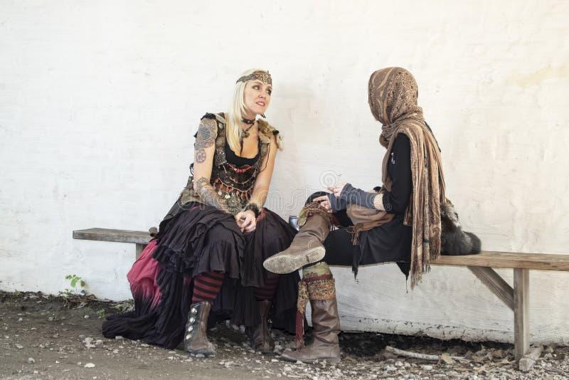 服装的两名美丽的妇女在长凳聊天对白色灰泥墙壁在马斯科吉Oklaho的俄克拉何马新生节日 免版税库存照片