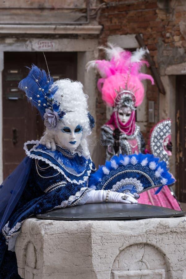 服装的被掩没的妇女有爱好者和华丽被绘的用羽毛装饰的面具的在威尼斯狂欢节 库存照片