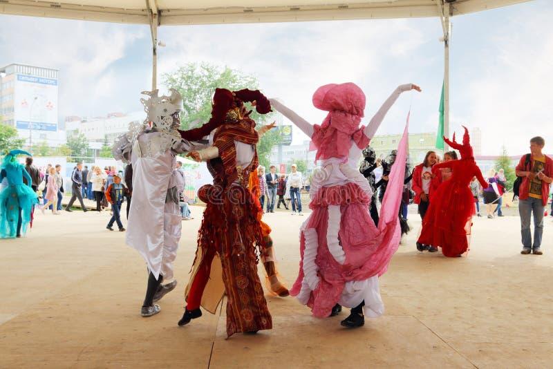 服装跳舞的人们在街道剧院在露天节日不眠夜里显示 免版税库存图片