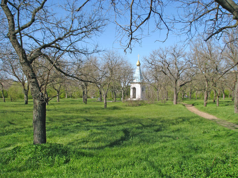 晴朗的天气的春天公园有基督徒教堂的看法 库存照片
