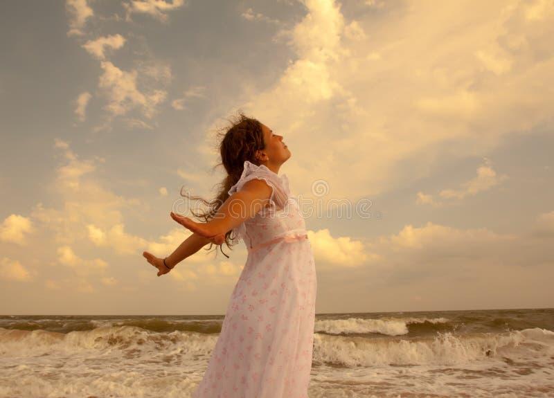 晴朗的海滩的美丽的女孩 自由和和平概念 图库摄影