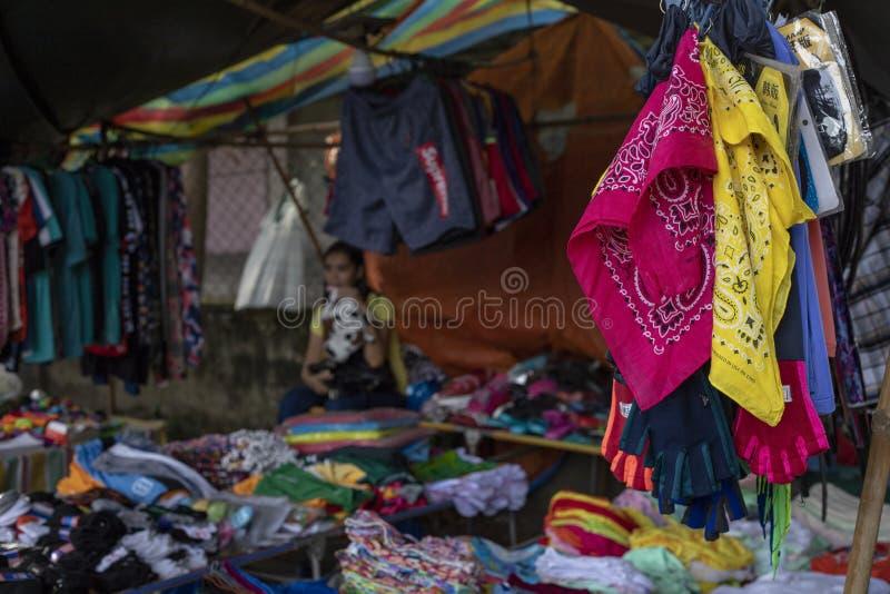 朗芒芽地,菲律宾- 2018年7月27日:在地方市场商店的便宜的五颜六色的衣裳 中间人穿戴摊位 图库摄影