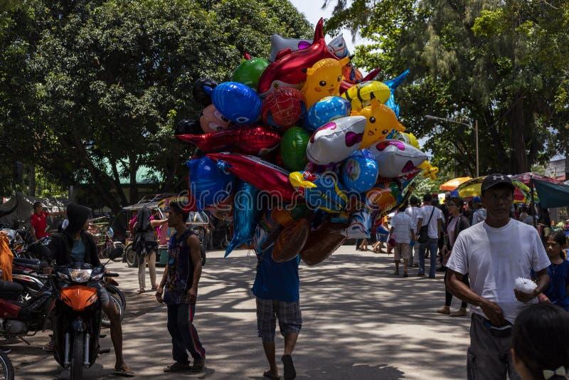 朗芒芽地,菲律宾- 2018年9月10日:庆祝地方节日节日的人们 五颜六色的气球卖主 库存照片