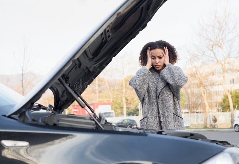 绝望妇女在检查汽车打破的引擎以后 库存照片
