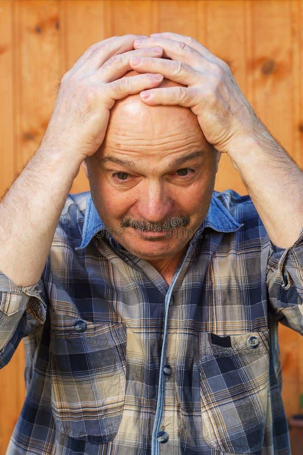绝望的年长人抓住他的头 免版税库存照片