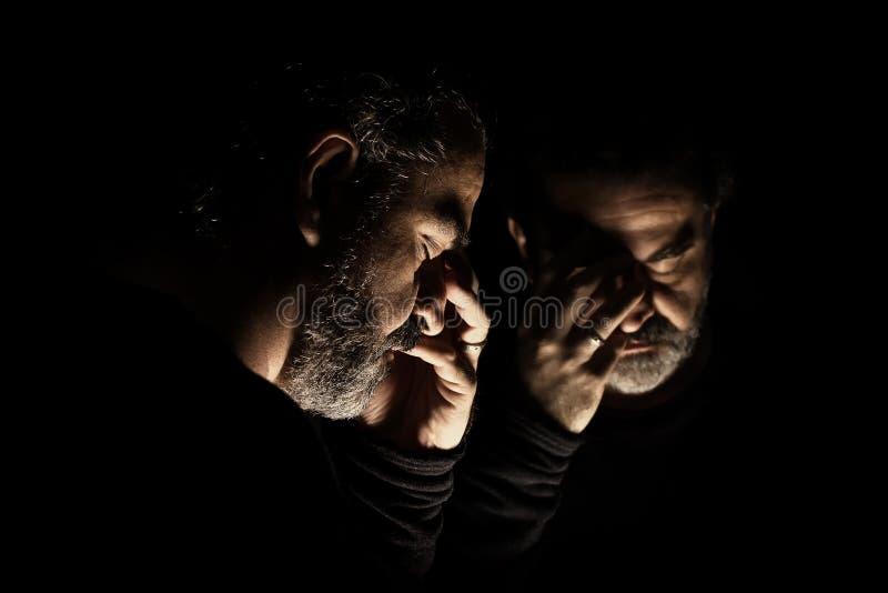 绝望,哀伤和偏僻的身分的人在镜子前面 免版税库存图片