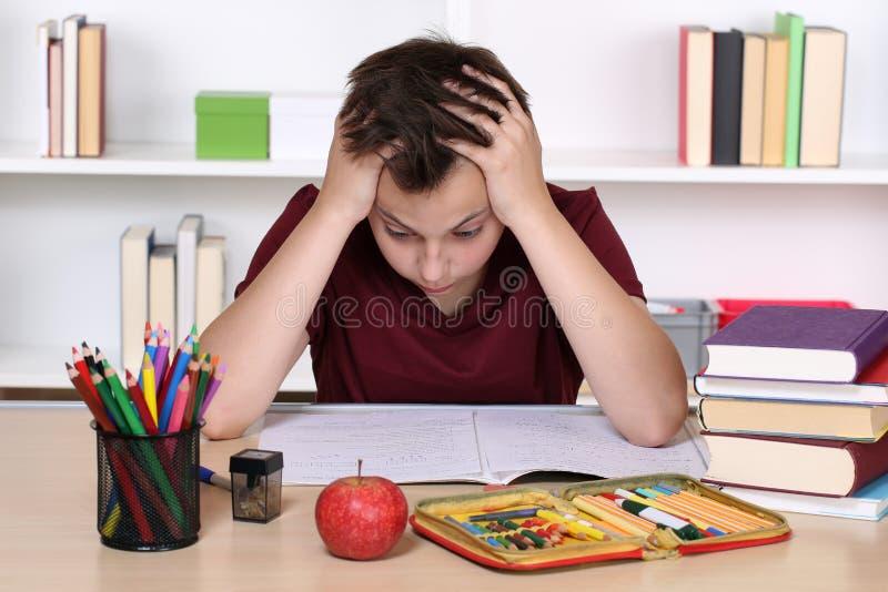 绝望年轻的学生,当做家庭作业时 图库摄影