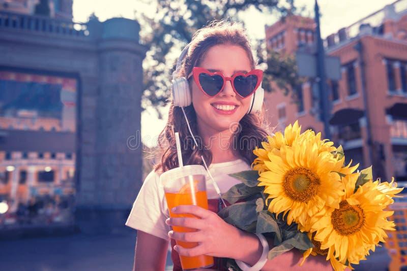 朝向对她的父母的有同情心的深色头发的女儿用美丽的向日葵 库存图片