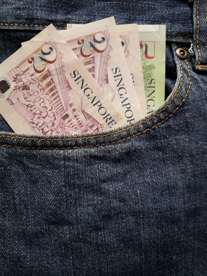 朝向牛仔裤的口袋的方法在蓝色的与新加坡钞票 库存照片