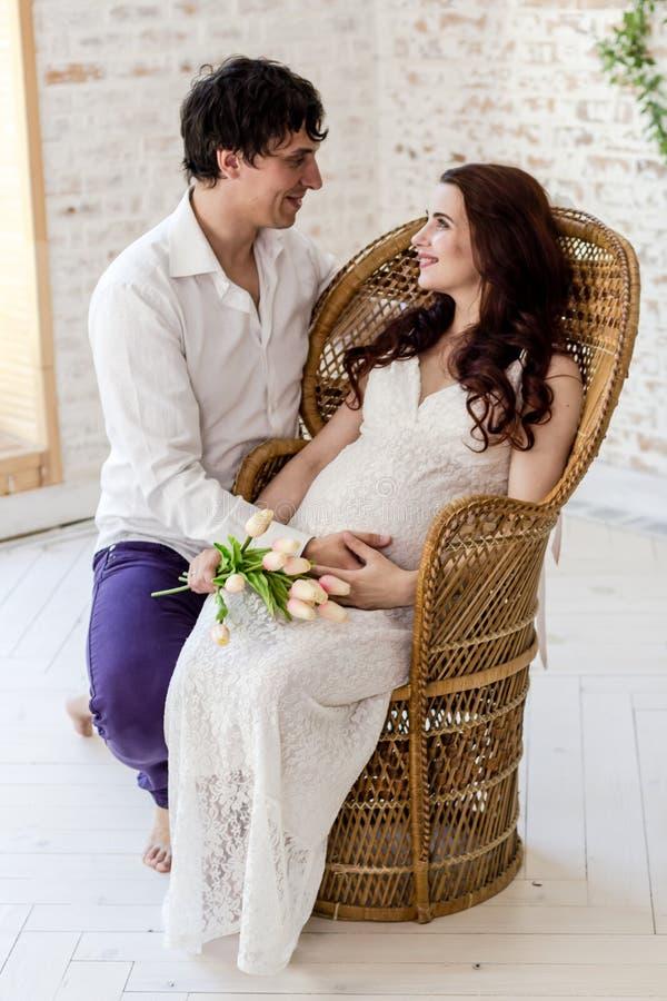 期待婴孩的年轻夫妇一起坐户内 库存图片