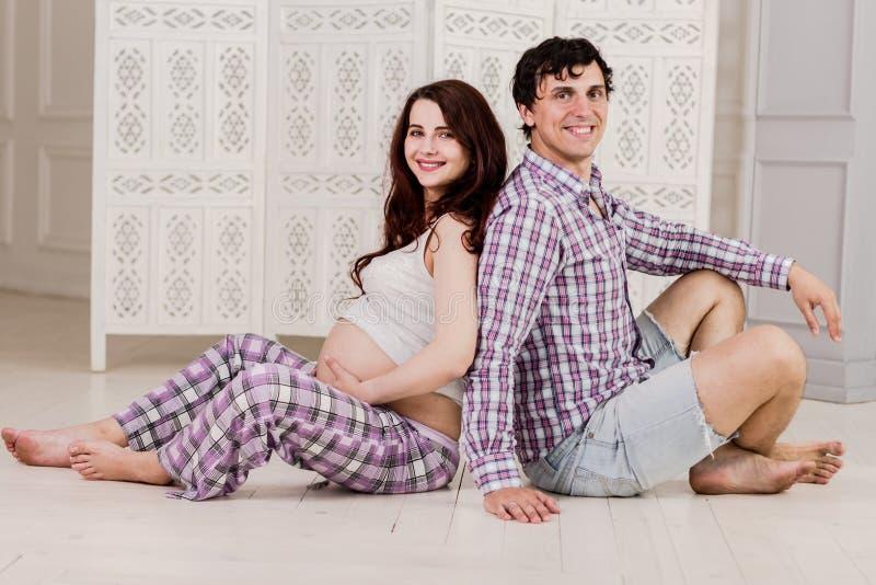期待婴孩的年轻夫妇一起坐户内 免版税库存图片
