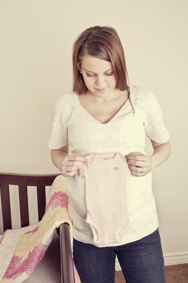 期待拿着新的婴孩的衣裳的母亲 免版税图库摄影