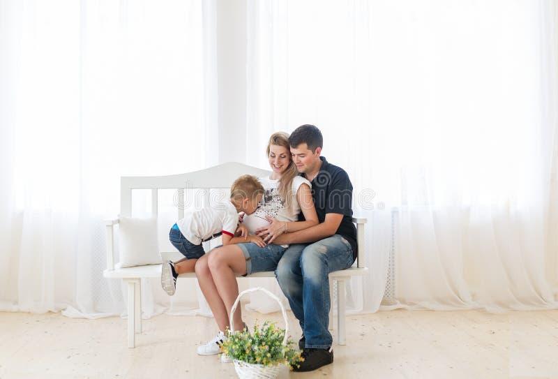 期待系列的婴孩新 儿童男孩感人的怀孕的母亲腹部 图库摄影