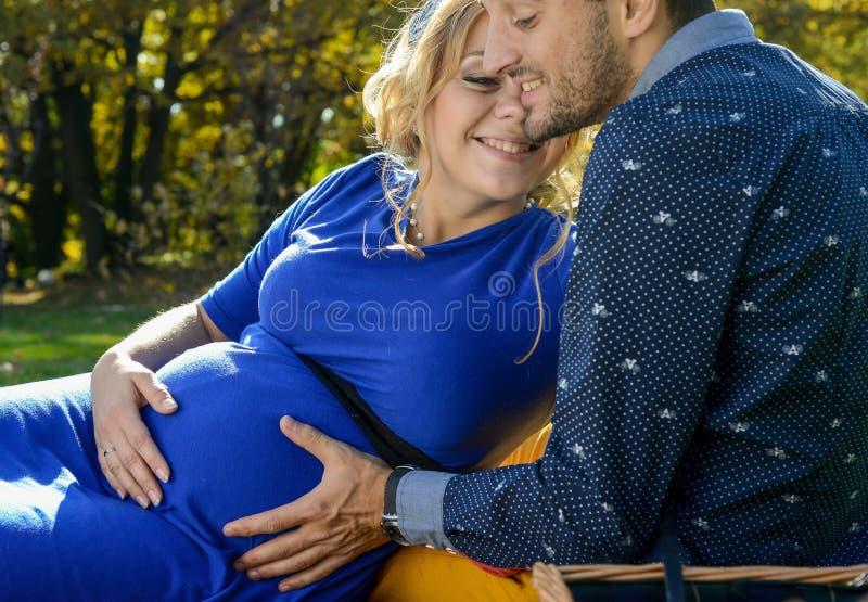 期待婴孩,感人的腹部的愉快的父母,坐绿草 库存图片