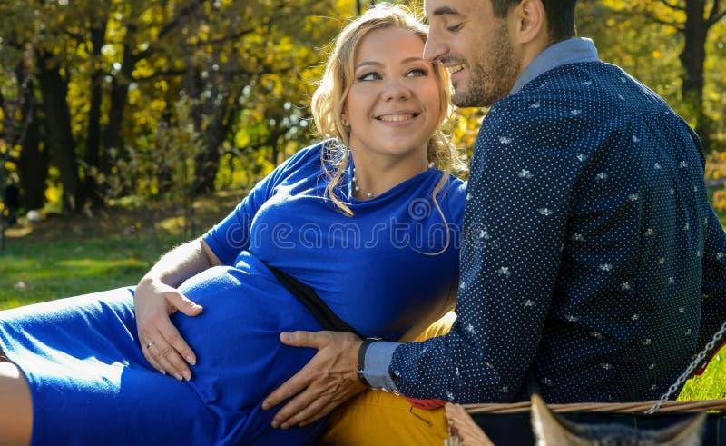 期待婴孩,感人的腹部的愉快的父母,坐绿草 免版税库存照片