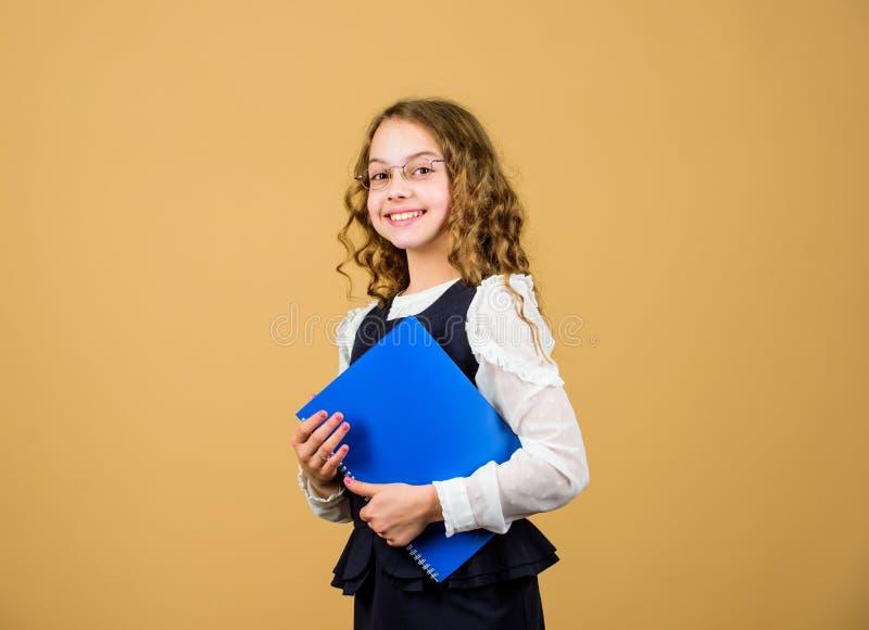 期末考试来 女孩举行课本准备对检查的文件夹测试在图书馆里 小儿童礼服 ?? 免版税库存图片