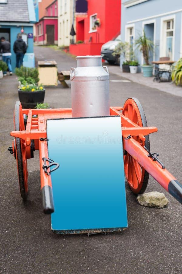 木两个轮子种田有铝罐的在幽谷镇街道的无盖货车和囤积居奇 免版税库存图片