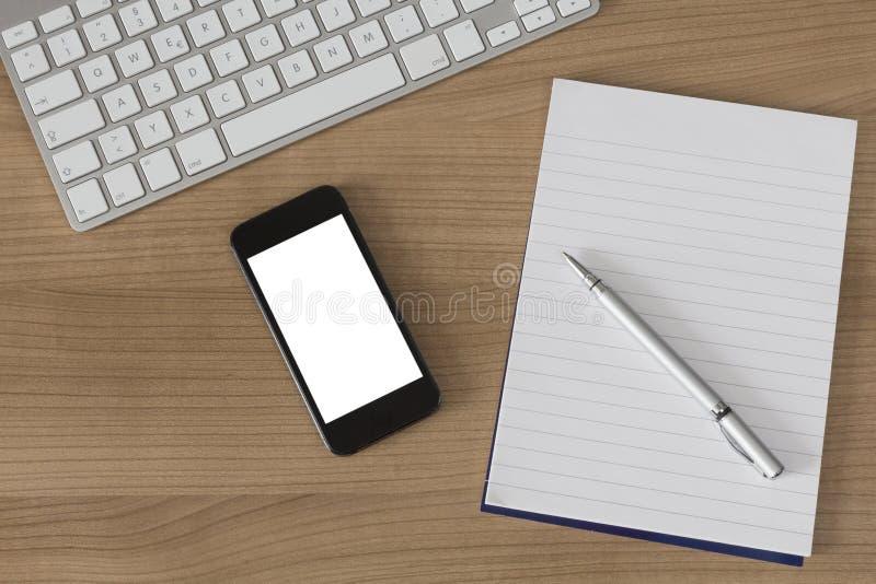 木书桌键盘智能手机和笔记薄 库存图片