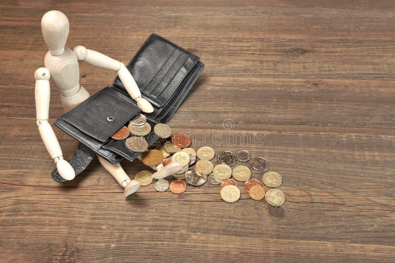 木人的小雕象、空的黑钱包和英国硬币, Ove 免版税库存照片