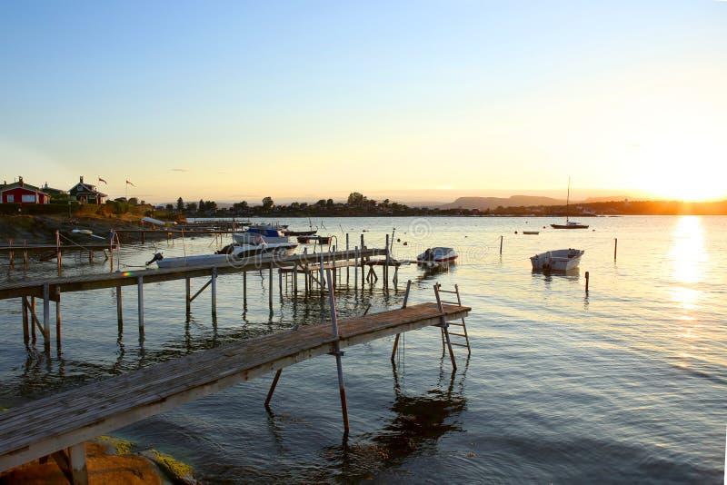木人行桥和汽船在日落的小游艇船坞 免版税图库摄影