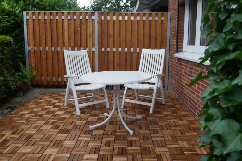 木分开和木瓦片、两把白色庭院椅子和圆桌在,与常春藤和金钟柏植物盖了,大阳台  免版税库存图片