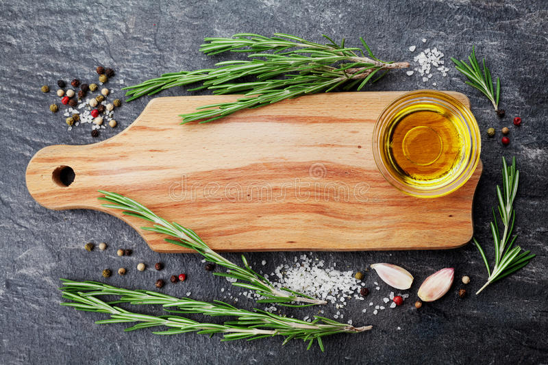 木切板、橄榄油、迷迭香植物、盐、大蒜和胡椒在黑桌上从上面食物的烹调背景或 免版税库存照片
